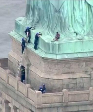 Vrouw beklimt Vrijheidsbeeld: 'Ik kom niet naar beneden tot alle kinderen zijn vrijgelaten'