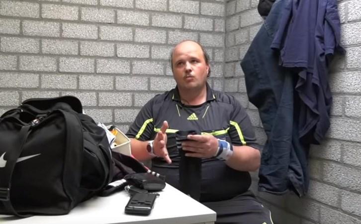 Parkeerwachter op voetbalveld bedreven in uitdelen prenten