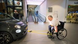 Hein Coumans trekt in rolstoel auto door  winkelcentrum Makado