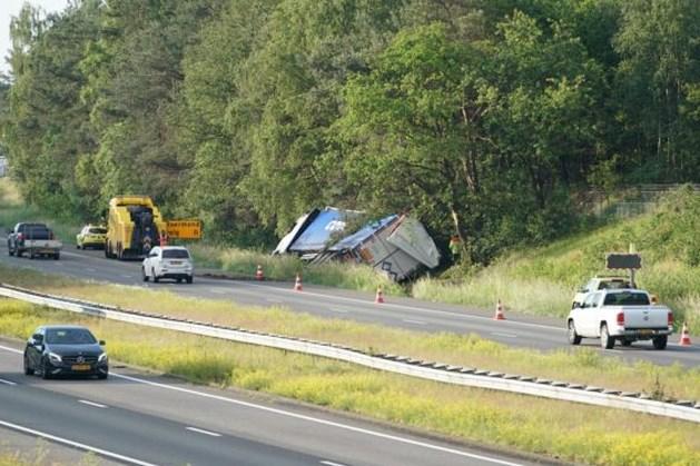Vrachtwagen met afvalproducten op zijn kant op A2