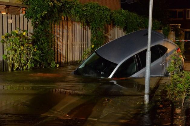 Auto verdwijnt half in zinkgat na waterleidingbreuk