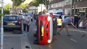 Auto op zijn kant na aanrijding: gewonde naar ziekenhuis