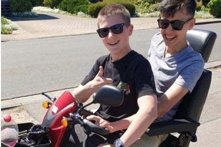 Twee bebrilde pikkies op een scootmobiel verjagen het coronaspook