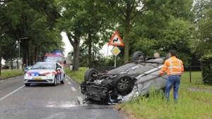 Auto slaat over de kop na botsing: twee gewonden
