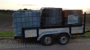 Aanhangwagen met drie grote vaten gedumpt in buitengebied