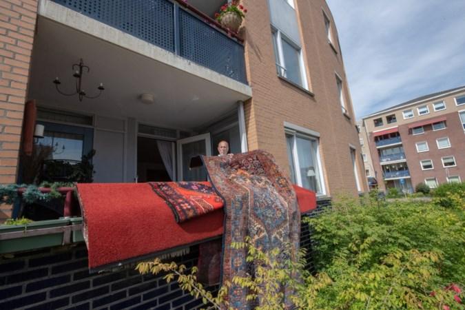 Tapijten hangen te drogen op het balkon na overvloed aan regenwater in Beek