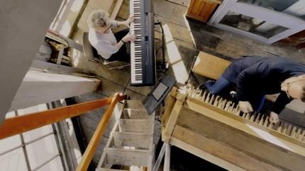 Duo sjouwt piano 30 meter naar boven om avondklok muzikaal uit te luiden met Clocks van Coldplay